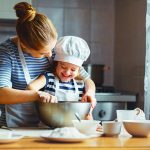 happy family in kitchen. mother and child preparing dough, bake cookies
